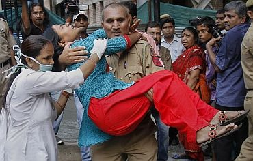 A nurse tries to assist as a policeman carries a woman, who was injured by a blast outside the high court