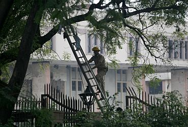 A police officer looks for evidence at the site of a bomb blast outside the Delhi HC