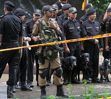 Commandos and police officers stand guard near the site of a bomb blast outside Delhi HC