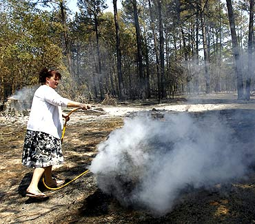 Shelly Silveira hoses down a burning log as she tries to prevent the fire from reaching her house