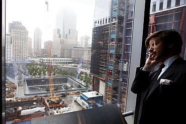 A journalist speaks on his phone as he looks down at the September 11 Memorial behind him during an event to update the public on the pace of development at the World Trade Center site in New York