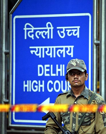 A police commando stands guard outside Delhi high court after Wednesday's bomb blast