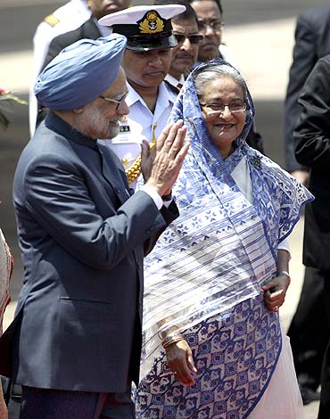 Prime Minister Manmohan Singh greets as Bangladesh's Prime Minister Sheikh Hasina watches after they arrive in Dhaka on September 6.
