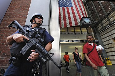 Members of the public react as they walk past a NYPD Hercules team on patrol near Penn Station in New York