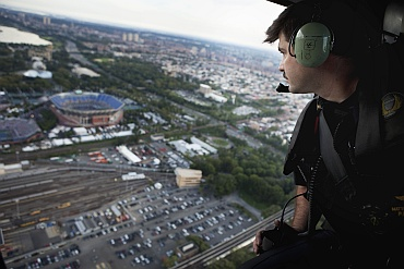 An NYPD officer looks down on the US Open Tennis tournament from a helicopter while on patrol above New York