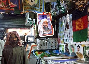A man walks past a poster of slain Al Qaeda leader Osama bin Laden on display for sale