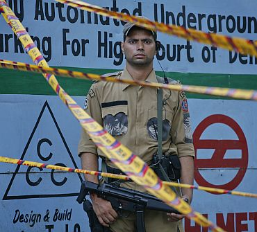 A SWAT member of the Delhi police force stands guard outside the high court after Wednesday's bomb blast
