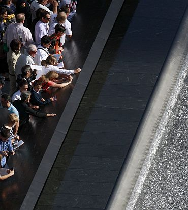 Family members look over one of the Twin Memorial pools at Ground Zero in New York