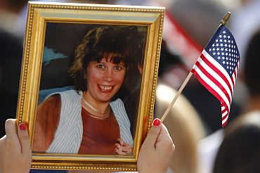 Person holds picture remembering victim of 9/11 attacks on World Trade Center during ceremonies marking 10th anniversary of attacks in New York