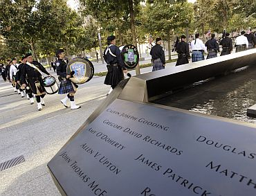 A line of bagpipers walk towards the stage past the North Pool at the National September 11 Memorial