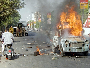 A man rides past a burning car during the 2002 riots in Ahmedabad