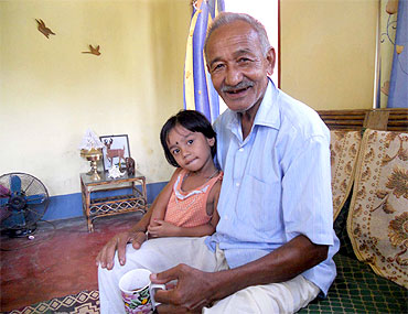 Suren Baruah, Anup Chetia's elder brother, with his grandchild at their home at Chokoli Bhoria village in Assam's Dibrugarh district