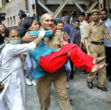 A policeman carries a woman, injured in the blast outside the Delhi high court, on September 7