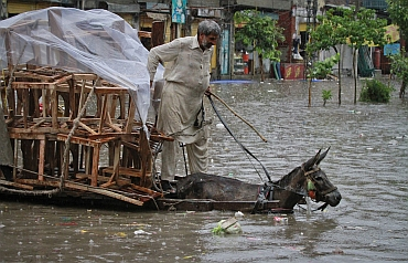 A man rides his donkey cart loaded with chairs through a flooded street, after a heavy downpour in Lahore
