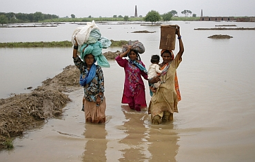 Villagers wade through flood waters with their belongings in the Tando Allahyar, district of Pakistan's Sindh province