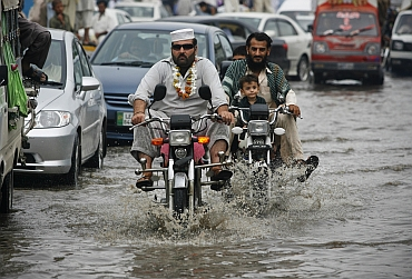 Residents ride motorcycles through a flooded street after heavy rains in Peshawar