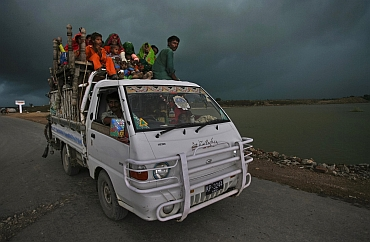 Monsoon clouds are seen as a family flee their flooded village in the Tando Allahyar district of Pakistan's Sindh province