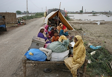 Villagers, who evacuated their flooded villages, sit on higher grounds with their belongings in the Tando Allahyar