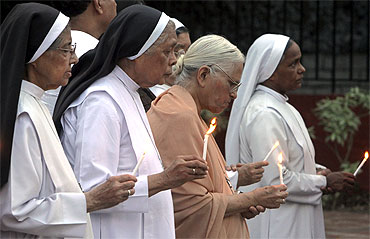 Women hold candles during a prayer ceremony for the victims of the Delhi HC blast