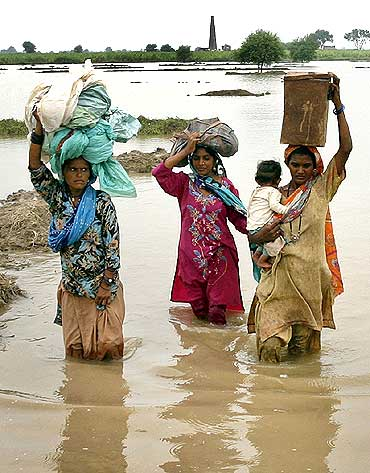 Villagers wade through flood waters with their belongings in the Tando Allahyar district of Pakistan's Sindh province on Monday