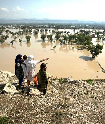 A family points towards partially submerged houses while taking refuge on a hilltop overlooking the flooded town of Nowshera, northwest Pakistan.