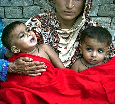 Twin boys in the arms of their mother who were born at a flood relief camp in Muzaffargarh district