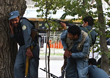 Afghan policemen fire towards a building which the Taliban insurgents took over during an attack near the US embassy in Kabul
