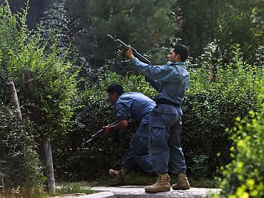 Afghan policemen fire towards a building which the Taliban insurgents took over