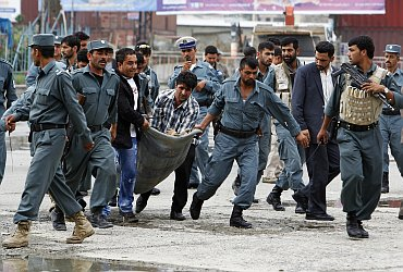 Afghan policemen carry a policeman who is a casualty at the site of an attack