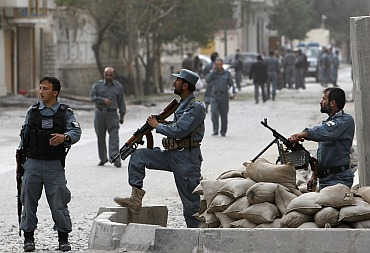 Afghan policemen keep watch at the site of the attack