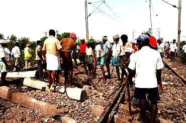 Railways workers clearing the debris at the site