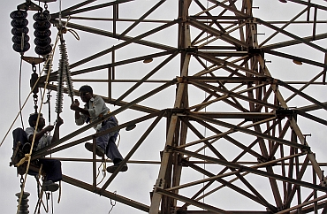 Employees of Gujarat Energy Transmission Corporation Limited work on a high transmission electric pylon on the outskirts of Ahmedabad