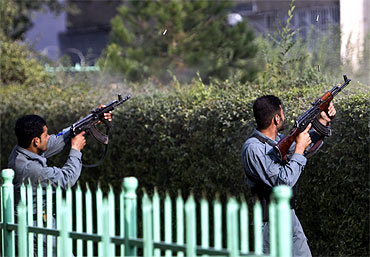 Afghan policemen fire at Taliban insurgents during an attack near the US embassy in Kabul