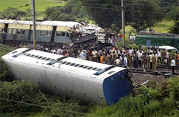 Railway officials and police work at the scene of a train collision between a passenger train and a