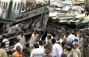 Railway officials and police stand in front of the damaged coaches of a passenger train