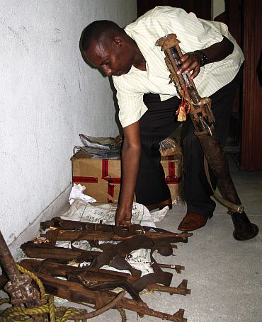 A Kenya Police officer arranges an exhibit of weapons used by suspected Somali pirates at the law court in Mombasa