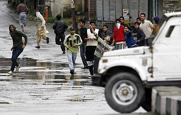 Protesters throw stones and pieces of bricks at an police vehicle in Srinagar