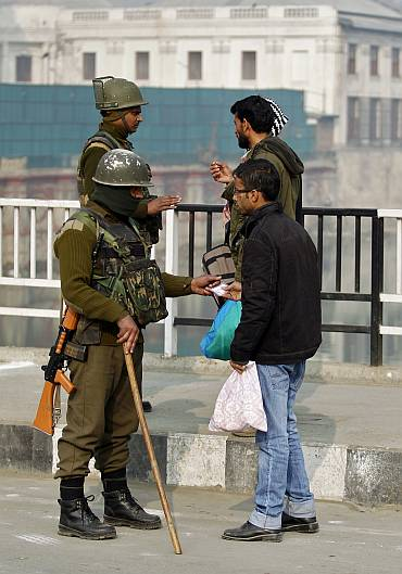 Policemen check Kashmiris at a barricade setup during a curfew in Srinagar