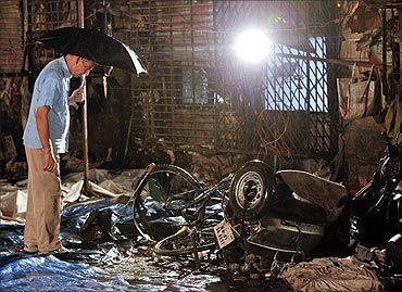 An investigator surveys the site of a blast in Zaveri Bazaar Mumbai