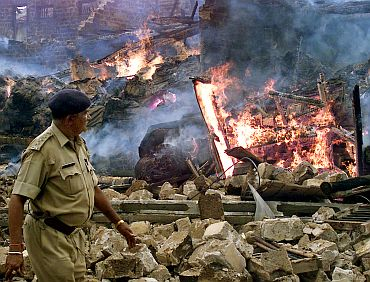 A policemen walks past a building which was burnt during the post Godhra riots in Gujarat
