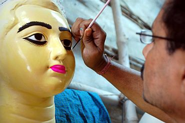 Artist Indrajit Paul of Kumartuli giving the final touches to an idol