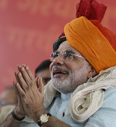 Modi wears an traditional Indian turban as he gestures to his supporters on second day of his fast