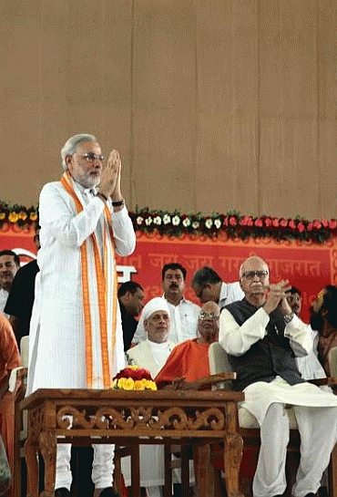 Modi greets his supporters while Advani looks on