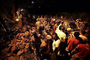 Members of the Nepalese army gather around a damaged car after the wall surrounding the British Embassy collapsed on top of the car that was passing by during the 6.8 magnitude earthquake that struck Kathmandu