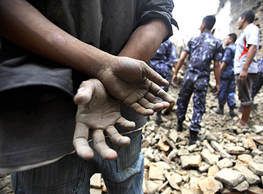 The hands of a resident are seen covered with mud as rescuers search for casualties in the ruins of a quake-damaged house at Lokanthali in Bhaktapur