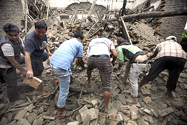 Residents search for casualties in the ruins of a quake-damaged house at Lokanthali in Bhaktapur