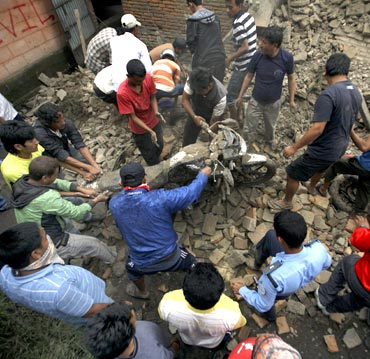 Residents remove a motorbike that was buried in the ruins of a quake-damaged house at Lokanthali in Bhaktapur
