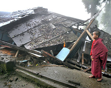 A monk looks over a damaged house in Gangtok