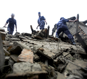 Nepalese police search for casualties in the ruins of a quake-damaged house at Lokanthali in Bhaktapur