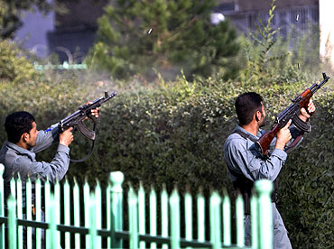 Afghan policemen fire toward a building which the Taliban insurgents took over during an attack